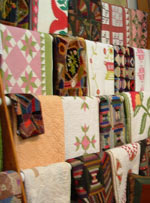 Image of quilts hanging on dowels for display, in the interior of the Rocky Mountain Quilts shop.